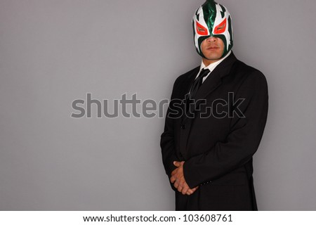 Man wearing a suit and luchador mask. - stock photo