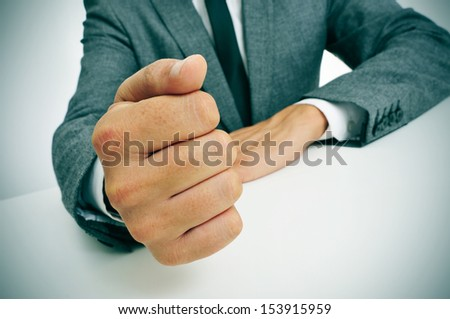 man wearing a suit banging his fist on the desk - stock photo