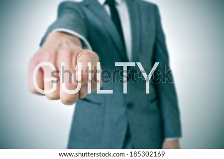 man wearing a suit pointing the finger to the word guilty written in the foreground - stock photo
