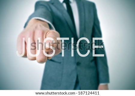 man wearing a suit pointing the finger to the word justice written in the foreground - stock photo