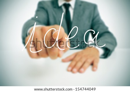 man wearing a suit sitting in a table pointing the finger to the word idea written in the foreground - stock photo
