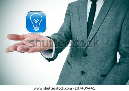 man wearing a suit with an icon with a light bulb in his hand - stock photo