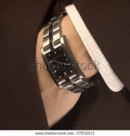 Man wearing a watch putting his hand in his suit pocket. - stock photo