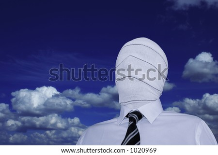 Man wearing a white shirt and a black and white striped tie with his face hidden under a bandage. + clipping path. - stock photo