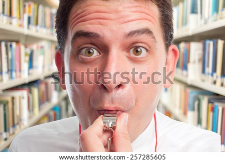 Man wearing a white shirt and using a whistle. He is looking funny. Over library background - stock photo