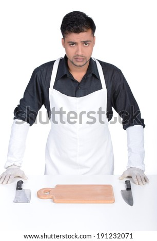 Man wearing apron holding knife. handsome butcher smiling and holding knife - stock photo