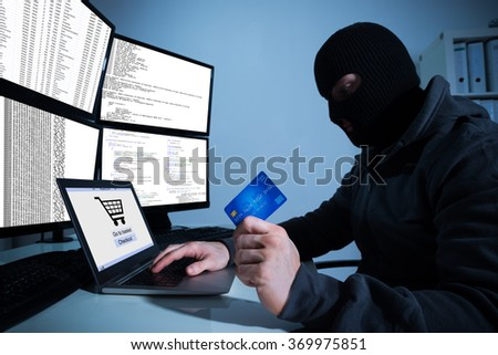 Man wearing balaclava and holding credit card while using laptop at desk - stock photo