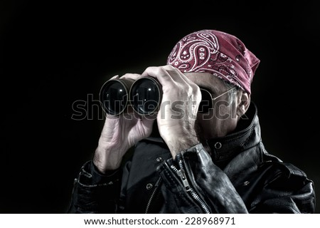 Man wearing bandana, sunglasses and leather jacket is looking through binoculars - stock photo