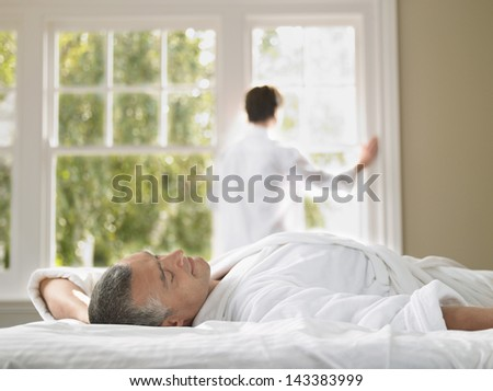 Man wearing bathrobe lying on bed with woman standing against window in bedroom