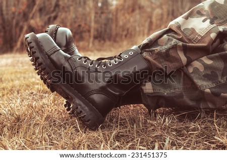 man wearing black leather boots - stock photo
