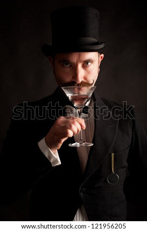 Man wearing black suit and top hat with a raised martini glass to his lips about to drink it. This image was shot with one light to give it drama and a grungy appearance