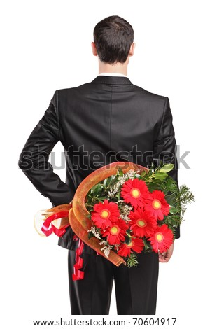 Man wearing black suit hiding a bouquet of flowers behind his back isolated on white background