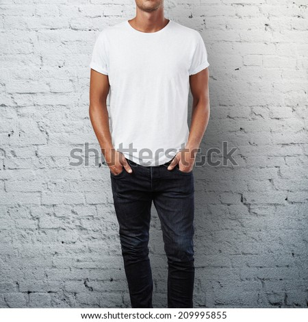 Man wearing blank t-shirt. Brick wall background - stock photo