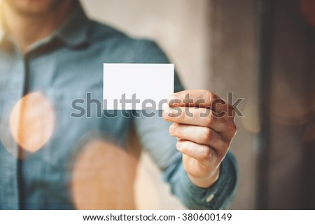 Man wearing blue jeans shirt and showing blank white business card. Blurred background. Horizontal mockup - stock photo