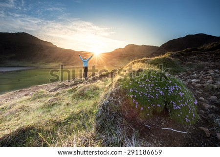 Man wearing blue shell jacket celebrating the sunset after a mountain hike, sun is setting behind a mountain range, and the last rays light up a small valley - stock photo
