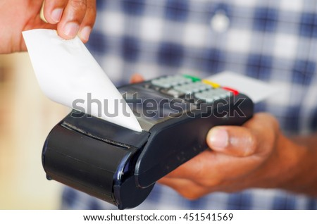 Man wearing blue white square pattern shirt processing payment using credit card terminal in front of camera, closeup angle