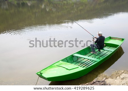 Man Wearing Cap And Vest Sitting In Green Rowboat And Fishing On The River - stock photo