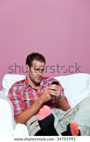 Man wearing casual clothing sat in an armchair text messaging on his mobile phone.