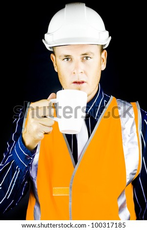 Man wearing construction helmet and drinks from white cup - stock photo