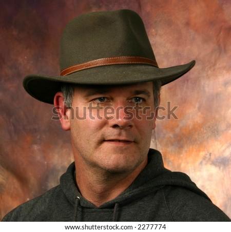 Man wearing cowboy hat unshaved - stock photo