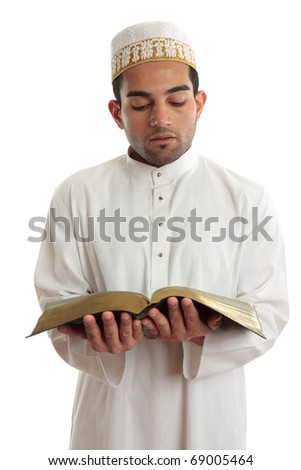Man wearing cultural clothing is reading or studying a religious holy book.  White background. - stock photo