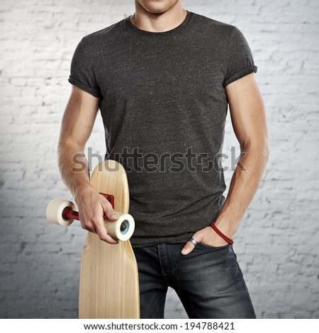 Man wearing dark grey t-shirt holding longboard in his hand