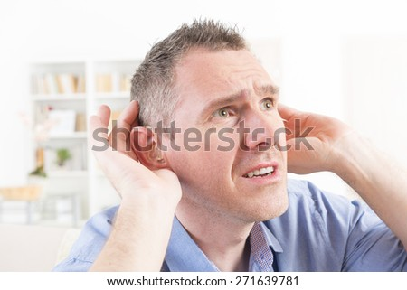 Man wearing deaf aid in ear attempting to hear something - stock photo