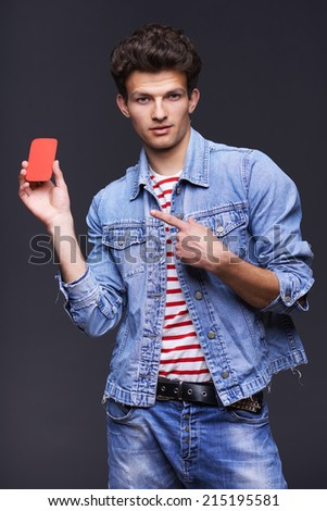 Man wearing denim jacket showing showing blank paper card sign with copy space for text, over gray background - stock photo