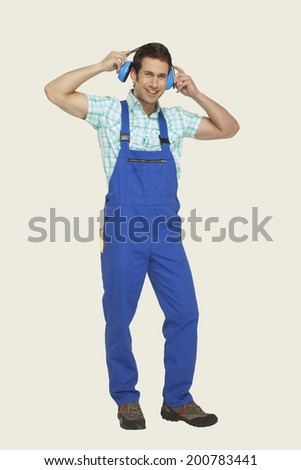 Man wearing ear muff smiling - stock photo