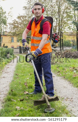 man wearing  ear protectors mowing grass in the backyard with petrol hedge trimmer - stock photo
