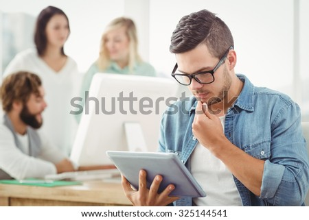 Man wearing eyeglasses using digital tablet at office