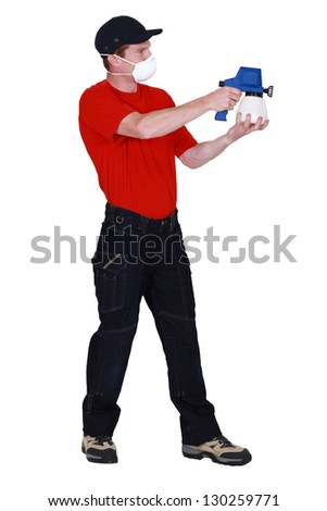 Man wearing face mask whilst using paint sprayer - stock photo