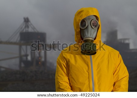 Man wearing gas mask standing infront of factory. Frontal shot. Background out of focus - stock photo