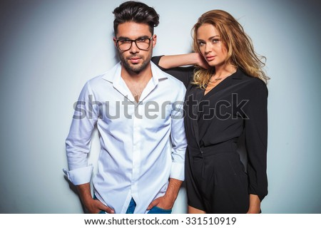 man wearing glasses pose with hands in pockets while woman rests her arm on his shoulder - stock photo