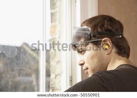 Man wearing goggles and earplugs, looking out window - stock photo