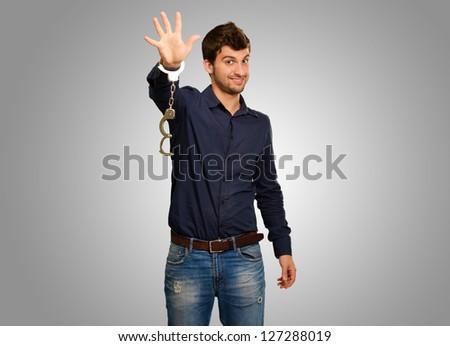 Man Wearing Handcuffs On Grey Background - stock photo