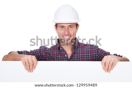 Man Wearing Hard Hat Holding Placard On White Background - stock photo