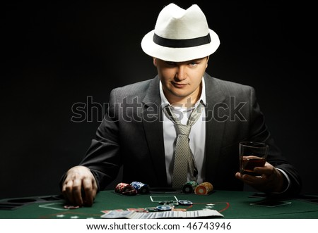 man wearing hat is playing poker in casino - stock photo