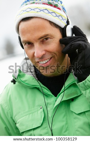 Man Wearing Headphones And Listening To Music Wearing Winter Clothes In Snowy Landscape - stock photo