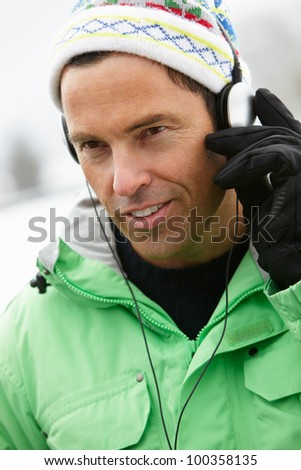Man Wearing Headphones And Listening To Music Wearing Winter Clothes In Snowy Landscape