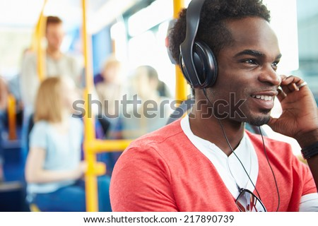 Man Wearing Headphones Listening To Music On Bus Journey - stock photo