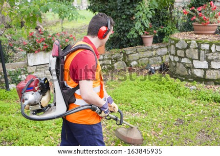 man wearing helmet and ear protectors mowing grass in the backyard with petrol hedge trimmer - stock photo