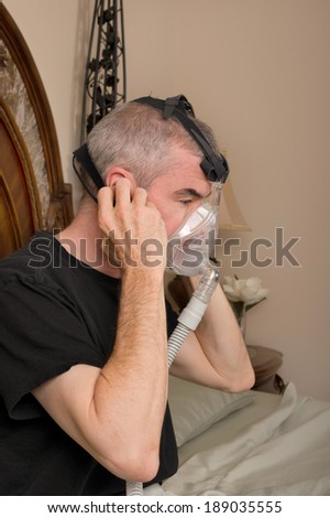 Man wearing his CPAP machine before sleeping - stock photo