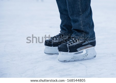 man wearing hockey skaters on ice rink