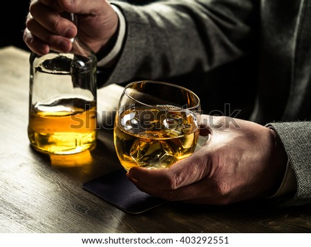 Man wearing jacket holding a glass of whiskey at the bar counter