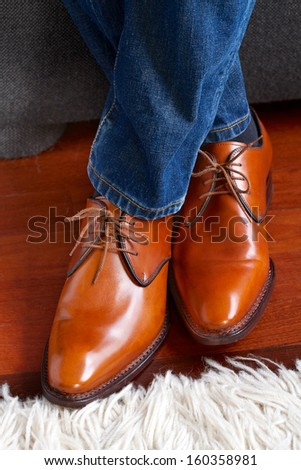 Man wearing jeans and brown leather shoes - stock photo