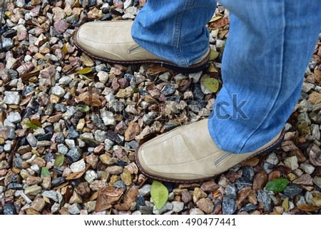 Man wearing jeans standing brown leather shoes on gravel.