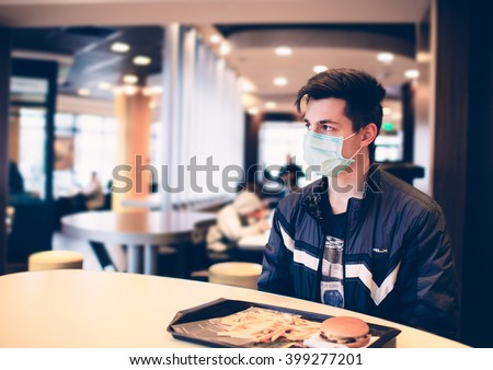 Man wearing medical face mask in the a restaurant. Male wearing face mask, protection from virus infection. - stock photo