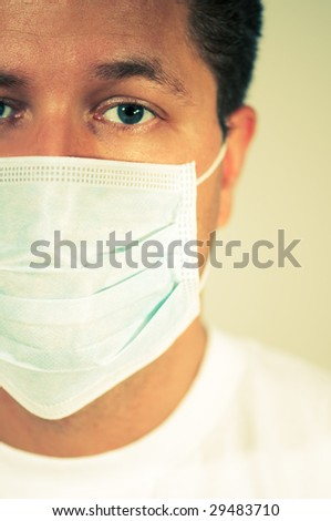 Man wearing medical mask with scared expression. - stock photo