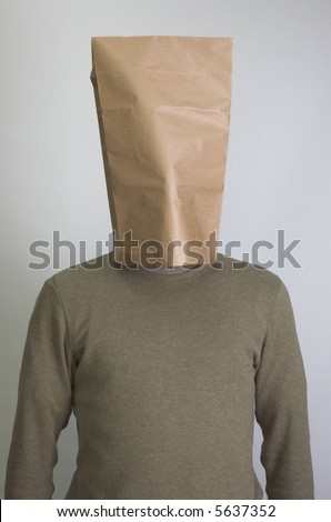 Man wearing paper bag on his head to hide from the world. - stock photo